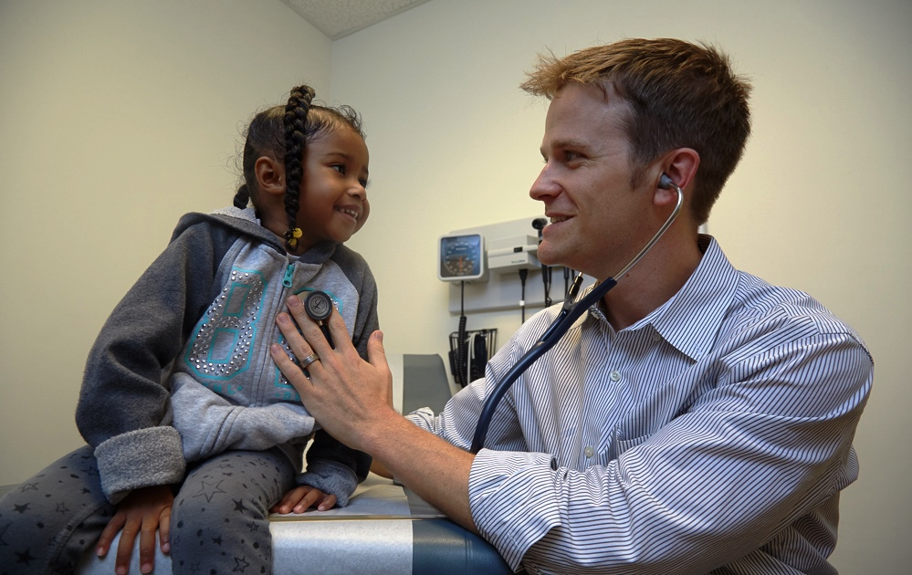 Medical doctor examining smiling child with stethoscope.